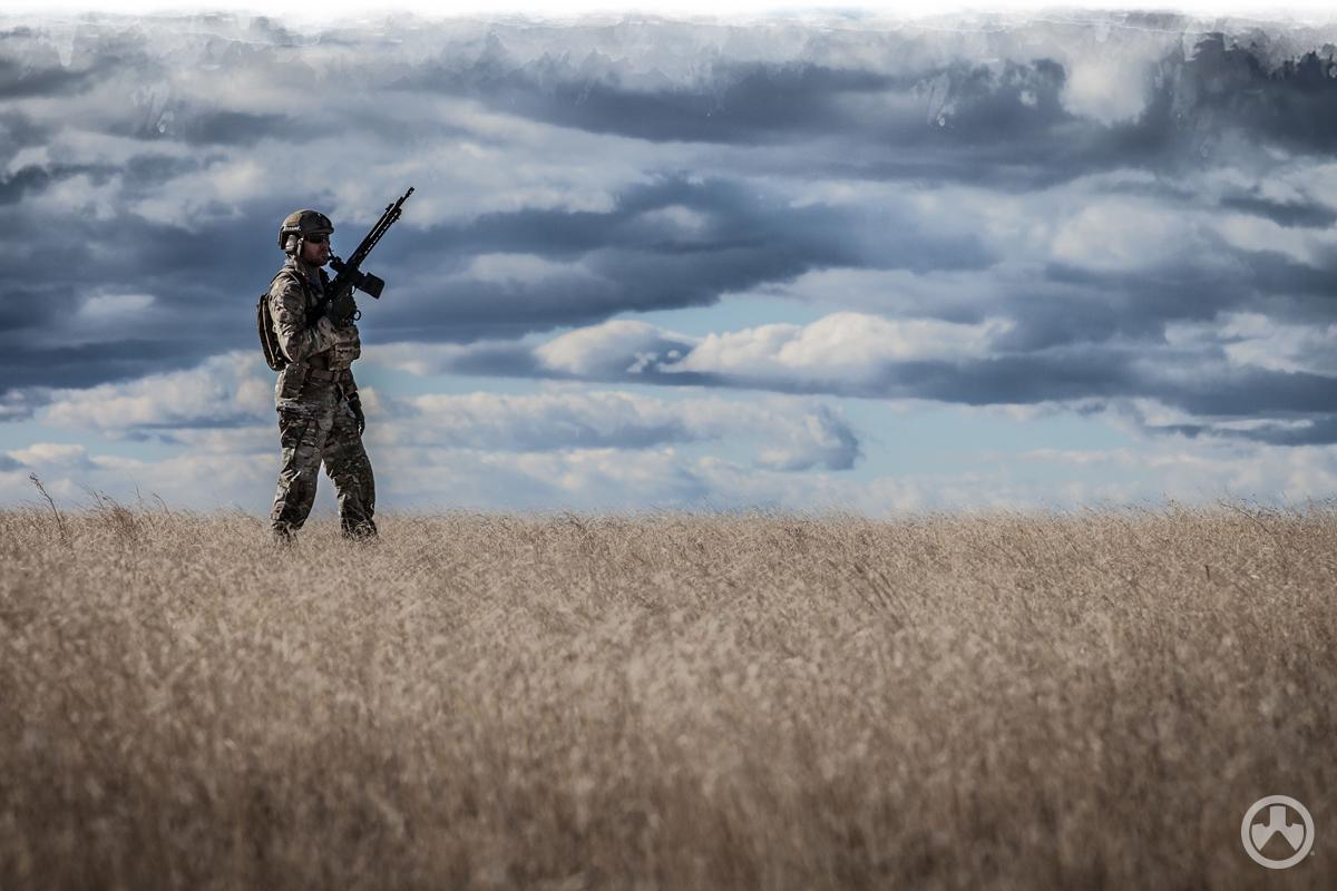 Man with firearm standing in field