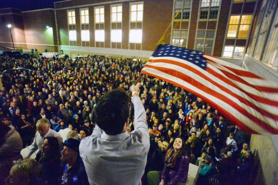Peter Wright holds an American flag above hundreds of people who were forced to organize in a parking lot during the caucus at East High school in Denver, Colorado on March 1, 2016. 18 precincts were represented at East High School and thousands of people turned out for the caucus. Organizers had anticipated about 20% of people from their precincts would turn out and many more actually came. (Photo by Helen H. Richardson/The Denver Post)