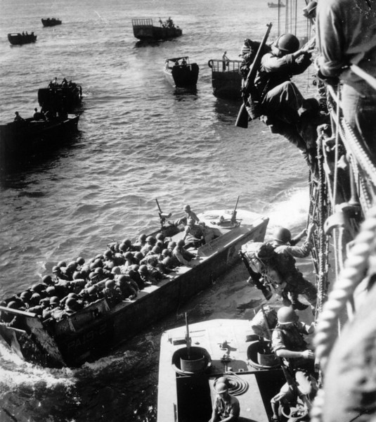 Description of  November 1943: As the invasion at Empress Augusta Bay gets under way on Bougainville, U.S. troops are seen climbing over the side of a Coast Guard-manned combat transport to enter the landing barges. (AP Photo)