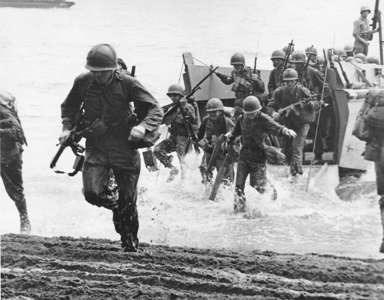 Description of  Aug. 1942: U.S. Marines, with full battle kits, charge ashore on Guadalcanal Island from a landing barge during the early phase of the U.S. offensive in the Solomon Islands during World War II. (AP Photo)