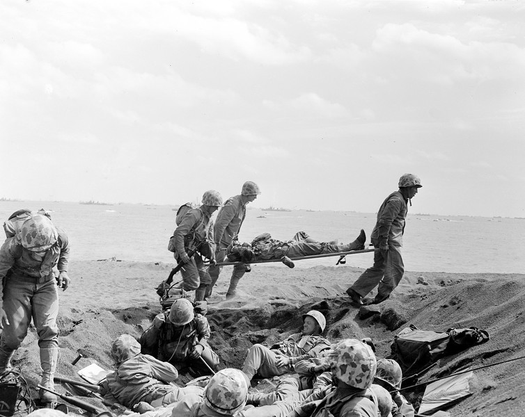 Description of  Feb. 25, 1945: U.S. Corpsmen carry a wounded Marine on a stretcher to an evacuation boat on the beach at Iwo Jima while other Marines huddle in a foxhole during invasion of the Japanese Volcano Island stronghold in World War II. The U.S. invasion fleet can be seen offshore. (AP Photo/Joe Rosenthal)