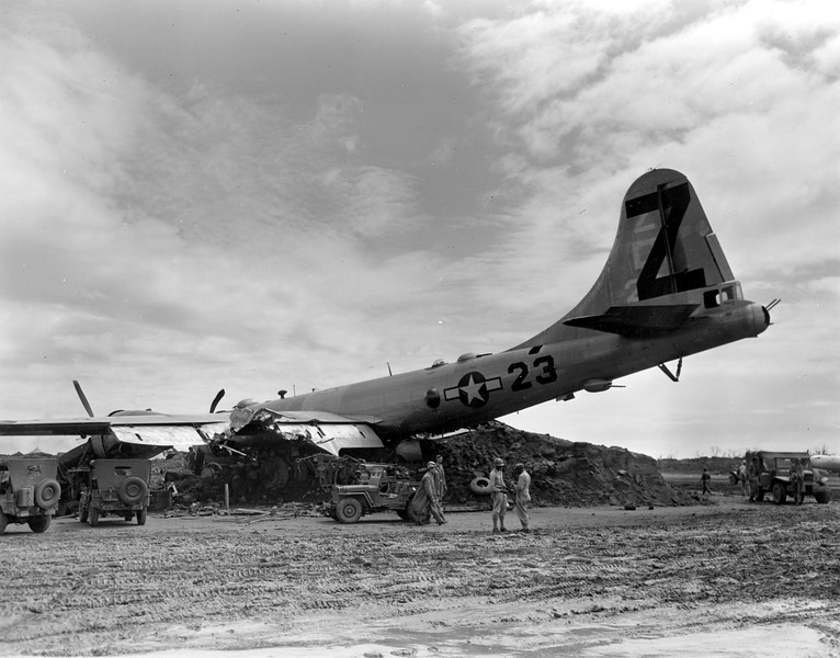 Description of  April 21, 1945: A B-29 Superfortress rests on a dirt mound after it crash landed with two engines working at Iwo Jima, Japan during World War II. The U.S. Air Force plane was damaged in a raid over Tokyo. (AP Photo/Murray Befeler)