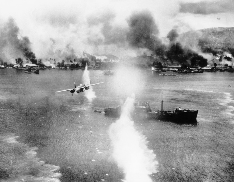 Description of  November 2, 1943: A B-25 bomber of the U.S. Army 5th Air Force strikes against a Japanese ship in the harbor at Rabaul, New Britain during an air raid on the Japanese-held air and naval base. (AP Photo)