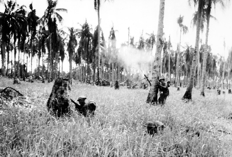 Description of  Feb. 1943: Soldiers of the Australian forces advance through a coconut grove and kunai grass in Japanese occupied New Guinea  during World War II. The smoke is from mortar fire during the fierce fighting in the final assault which took Buna, the Japanese stronghold.  (AP Photo)