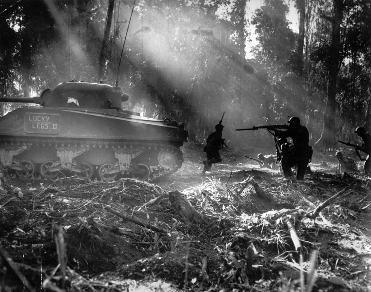 Description of  March 1944: Following in the cover of a tank, American infantrymen secure an area on Bougainville, Solomon Islands after Japanese forces infiltrated their lines during the night. (AP Photo)