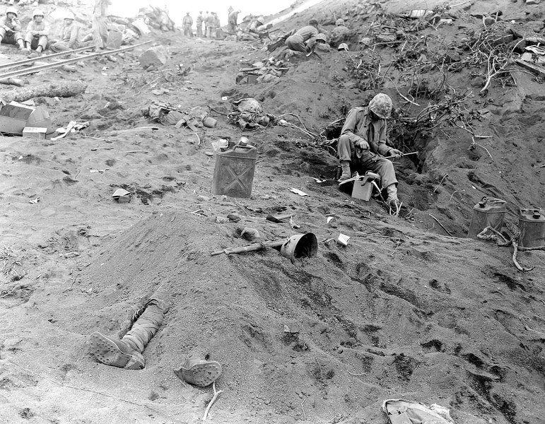 Description of  February 1945: The booted feet of a dead Japanese soldier, foreground, protrude from beneath a mound of earth on Iwo Jima during the American invasion of the Japanese Volcano Island stronghold in World War II. U.S. Marines can be seen nearby in foxholes. (AP Photo/Joe Rosenthal)