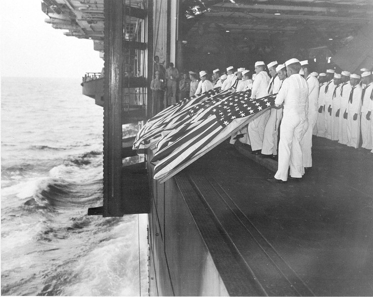 Description of  Nov. 26, 1944: Burial at sea ceremonies are held aboard the USS Intrepid for members of the crew lost after the carrier was hit by a Japanese suicide pilot while operating off the coast of Luzon, the Philippines, during World War II. Sixteen men were killed in the kamikaze attack. (AP Photo/U.S. Navy)