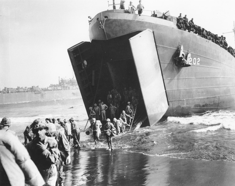 Description of  January 1944: U.S. Marines come ashore from the mouth of a Coast Guard manned LST, during the invasion of New Britain Island, at Cape Gloucester. (AP Photo)