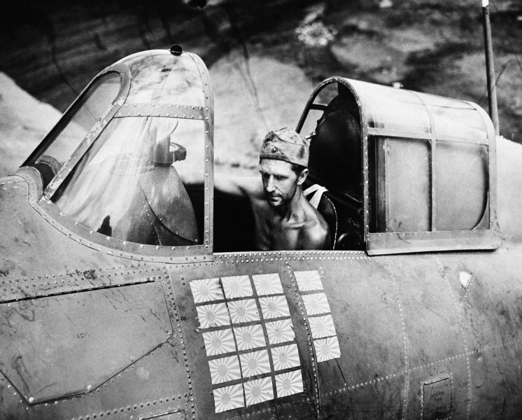 Description of  March 22, 1943: Technical Sgt. R.W. Greenwood, a Marine, sits in the cockpit of a Grumman Wildcat fighter plane, based at Henderson Field, Guadalcanal, that is credited with shooting down 19 Japanese aircraft, as illustrated by the number of Japanese flags on his plane. Several different pilots have flown the ship during successful missions, but Sgt. Greenwood has remained plane captain. (AP Photo)