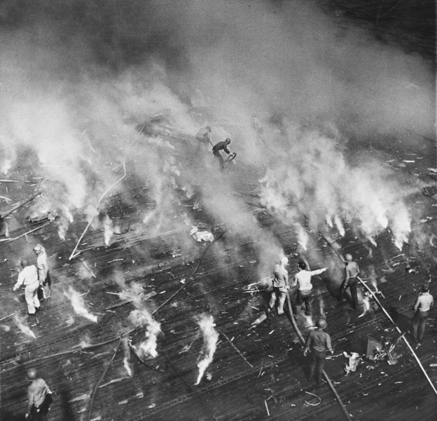Description of  Nov. 25, 1944: Firefighters are almost hidden by smoke as they turn their hoses on many small fires started on the flight deck of the USS Intrepid after a Japanese suicide plane crashed into the carrier while it was operating off the coast of Luzon, the Philippines. (AP Photo/U.S. Navy)