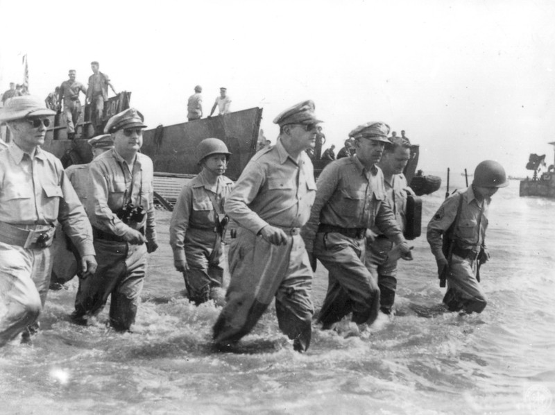 Description of  October 20, 1944: Gen. Douglas MacArthur, center, is accompanied by his officers and Sergio Osmena, president of the Philippines in exile, extreme left, as he wades ashore during landing operations at Leyte, Philippines, after U.S. forces recaptured the beach of the Japanese-occupied island. To his left is Lt. Gen. Richard K. Sutherland, his chief of staff. (AP Photo)