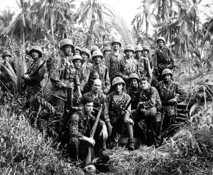 Description of  January 1944: These U.S. Marine Raiders, with the reputation of being skillful jungle fighters, pose in front of a Japanese stronghold they conquered at Cape Totkina, Bougainville. (AP Photo)