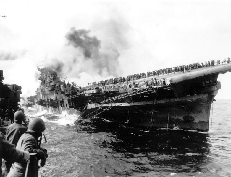 Description of  March 19, 1945: The USS Santa Fe lies alongside the heavily listing USS Franklin to provide assistance after the aircraft carrier had been hit and set afire by a single Japanese dive bomber, during the Okinawa invasion off the coast of Honshu, Japan. (AP Photo)