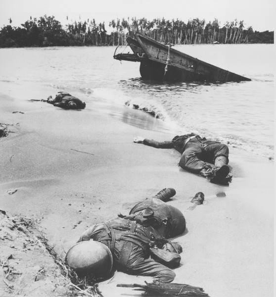 Description of  January 1943: The bodies of three American soldiers, fallen in the battle for Buna and Gona, lie on the beach of the island in the Papua New Guinea region during World War II.  (AP Photo)