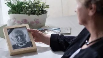 picture of widow looking a photo of her deceased husband