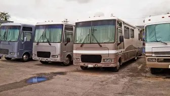 A row of large RVs for sale on a dealer's lot