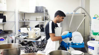 picture of young man washing dishes in a restaurant
