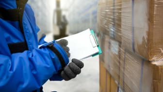 A man bundled up in warm clothes checks an order sheet in a cold-storage facility