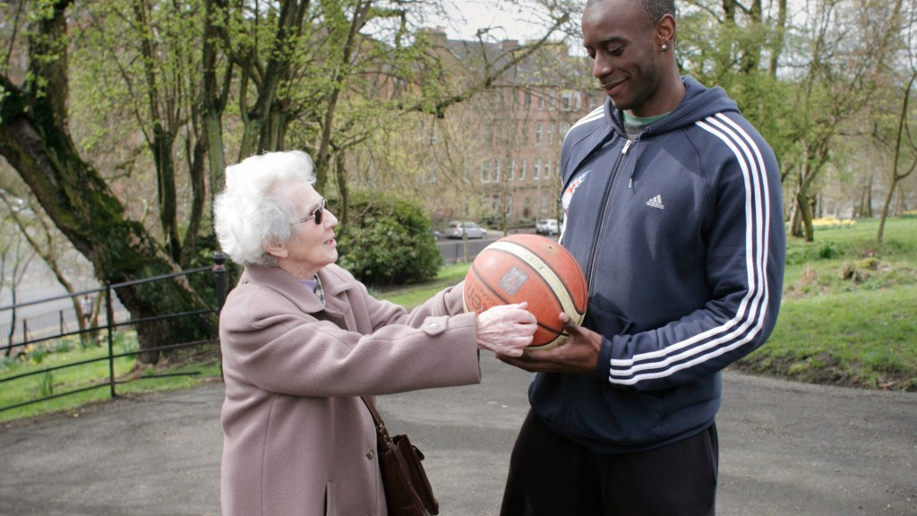 Older lady and man wearing sports clothes handing a basketball to each other