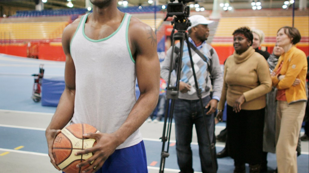 Basketball player standing for photo with production participants and camera in background