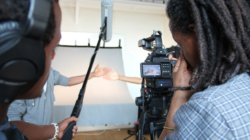Close up of participants filming with a shot of two peoples' hands, palm forward, touching each other