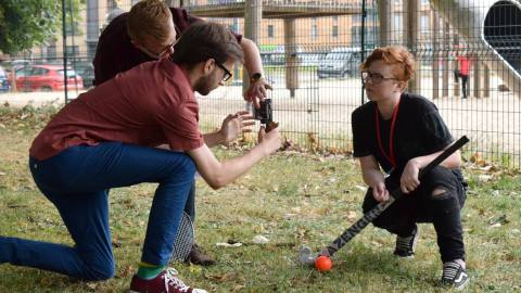 Two men filming a girl crouched down with hockey stick on a mobile phone