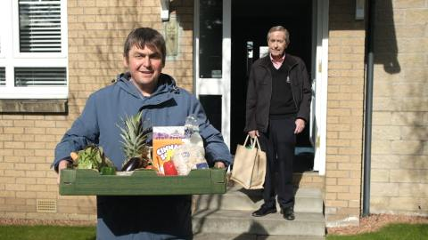 A man holding a box of fruit and vegetables stands in front of an older man holding a bag of shopping in the doorway of his home.