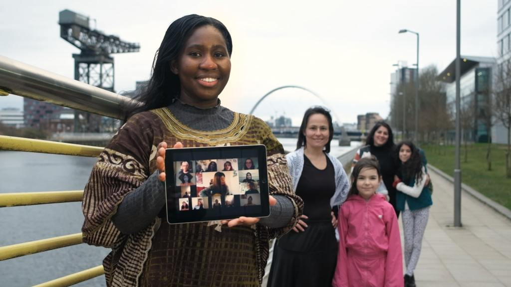 A young black woman holds an iPad which shows a choir singing together. Behind her are a group of other young women of colour. They are all standing beside the River Clyde.