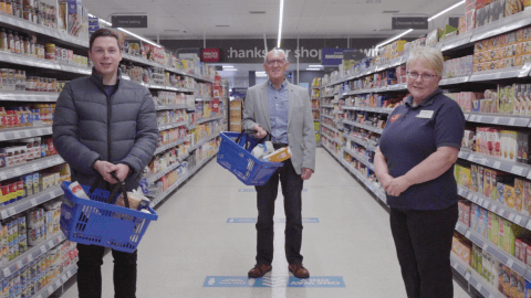 Two men and a woman stand in a supermarket holding baskets and smiling at the camera.