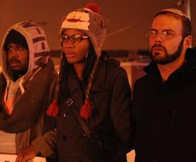 Ka'milla McMiller (center) links arms with two other protesters to block the intersection of Kingshighway and Manchester Ave on November 26.