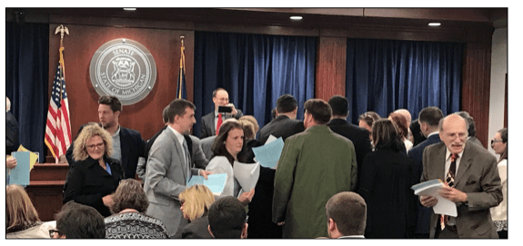 Lobbyists, staffers and others at Senate committee meeting room on April 18 collect paperwork showing the details of the Senate's initial budget proposal for next year for DHHS.