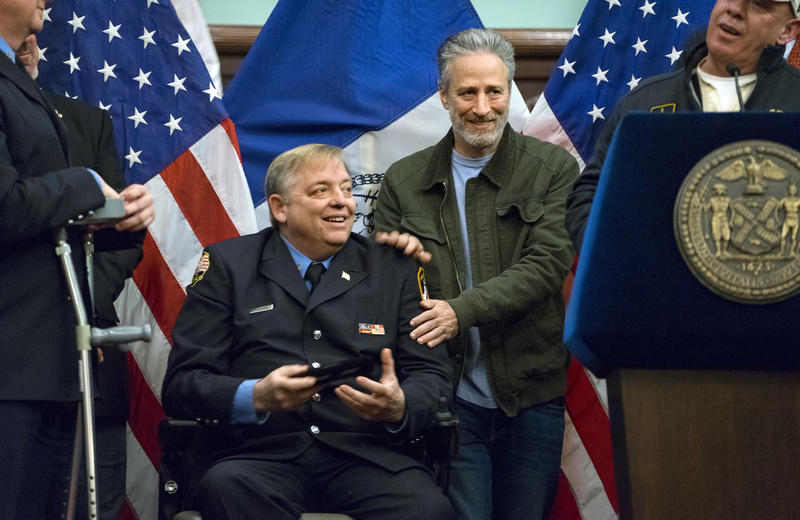 Comedian Jon Stewart stands behind retired FDNY firefighter and Sept. 11 first responder Ray Pfeifer after Pfeifer was given the key to New York City in 2016. Pfeifer passed away in 2017 from cancer related to his work at the World Trade Center site.