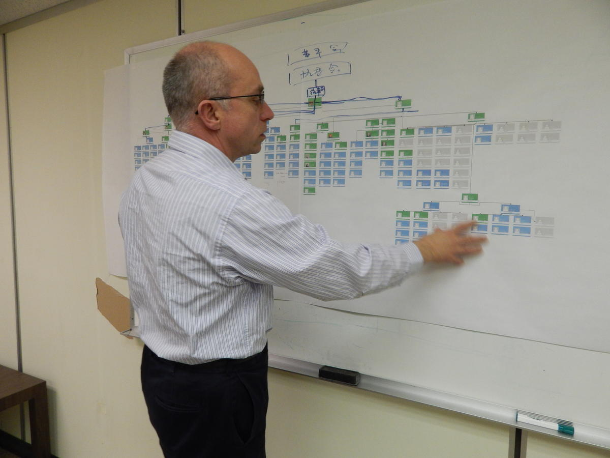John Gauthier, president of Fuyao Glass America, gestures towards a chart of leadership positions still to be filled at the company.