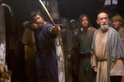 Moses (Christian Bale) displays his prowess with a bow and arrow, as Joshua (Aaron Paul, center) and Nun the scholar (Ben Kingsley) watch.