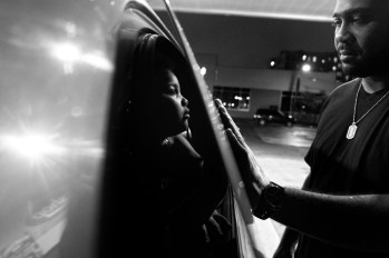 Billy Garcia enjoys a tender moment with daughter Esmeralda while pumping gas. Bronx, NY.