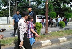 Anggota Kepolisian menggiring 1 orang wanita pendukung ahok yang melakukan aktifitas mirip dukun, selasa (3/1/2017) (Net)