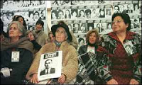 Relatives of Chile's missing dissidents watch televised reports of the hearing in London