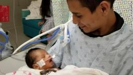 Inside a Chicago-area hospital, a baby boy remains in grave condition after his mother was killed. But a photo has emerged of him with his father.