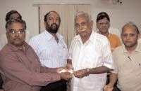 Sivaraman (left) hands over a health card to a teacher