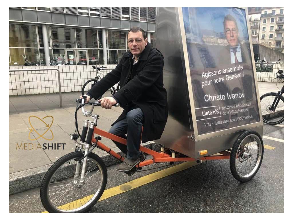 Christo Ivanov candidat au conseil municipal de la ville de Genève, roule avec les vélos électriques publicitaires MediaShift .