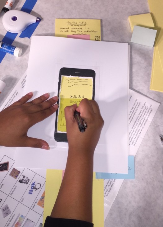 A cut-out of an iPhone 6 Plus takes center stage in prototyping where students use paper to create new features and screens for a web-based long-form project that they redesign for mobile use.
