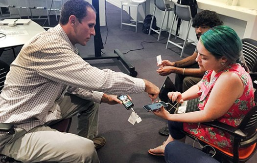 Guest speaker and startup entrepreneur Eric Ortiz shows JEDI student manager Monica Castillo how to use Evrybit during the mobile and emerging platforms class at USC in fall 2015.