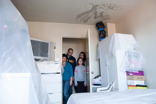 The Santana family puts plastic over their belongings because of ceiling leaks. Photo by María Villaseñor.