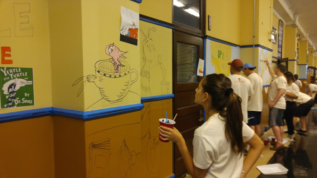 About a dozen 20-somethings painting an elementary school hallway.