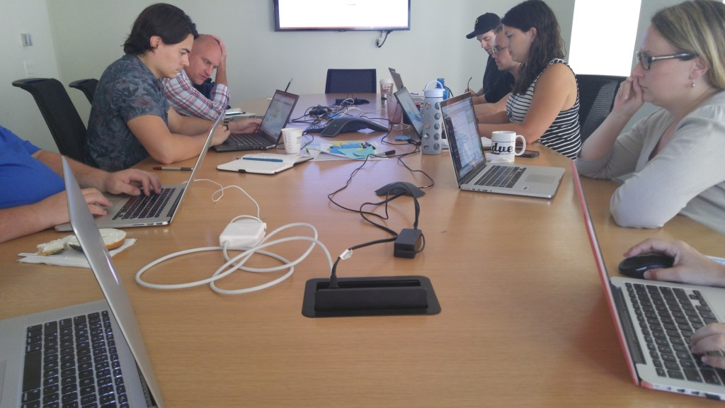 This shows six people around a speakerphone with their laptops out and water bottles at the ready. Most are starting at their computer screens. Mostly Macs.