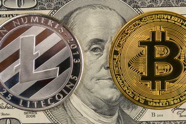 Litecoin symbol on a silver coin and bitcoin symbol on a gold coin.