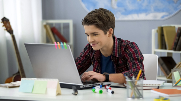 Young Teen boy looking at his laptop screen.