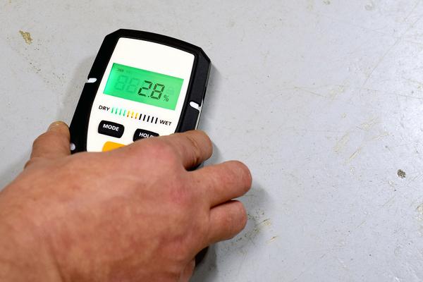 Man using a moisture meter on a wall