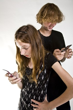 Two teens texting on their phones.