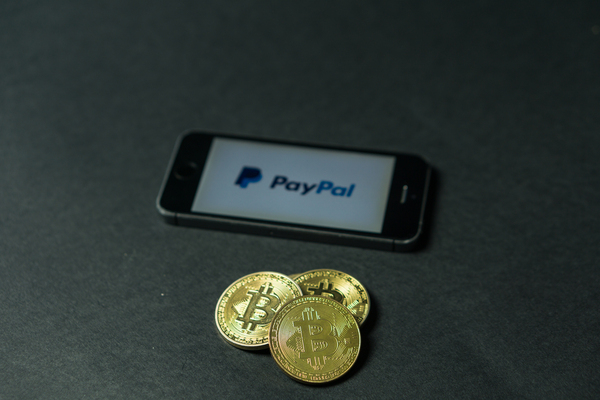 Bitcoin gold coins and a mobile phone displaying the paypal app.
